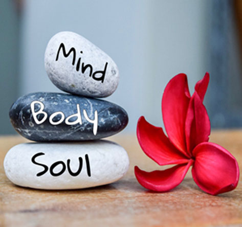rocks showing words stating mind, body and soul with a flower on the desk